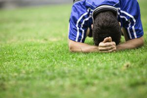 Soccer Player with Head Down on Grass